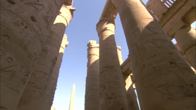 the columns of the karnak temple contrast with  a bright blue sky. - temples of karnak stock videos & royalty-free footage