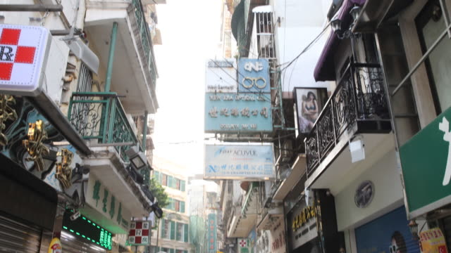 the commercial signs written in chinese over a narrow pedestrian commercial zone where the shops are still closed because of the early morning - ein tag im leben stock-videos und b-roll-filmmaterial