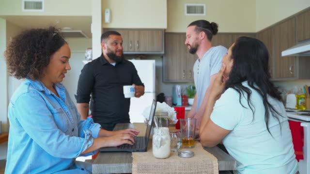 vídeos y material grabado en eventos de stock de la compañía de los millennials, jóvenes amigos de diferentes etnias y géneros, comiendo, hablando, riendo y trabajando alrededor de la mesa en un apartamento compartido de alquiler. - compartir