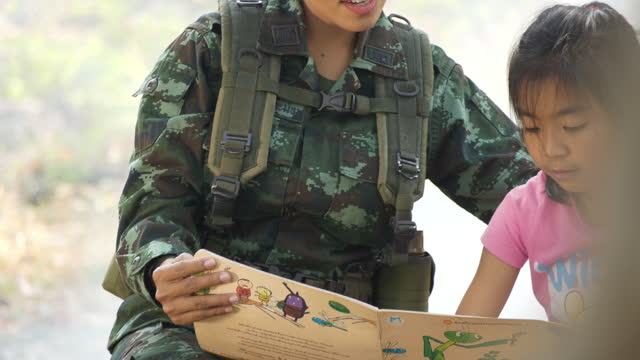 the concept of military training operations.a female soldier doing a book with a child - homecoming stock videos & royalty-free footage