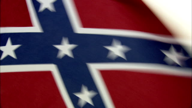 the confederate flag flaps in the wind. available in hd. - confederate flag stock videos and b-roll footage