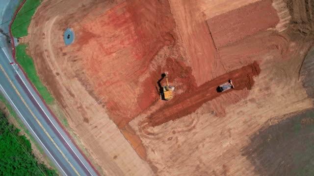 vídeos de stock, filmes e b-roll de a terraplanagem da construção: achatamento do lugar de construção, com a maquinaria de construção, escavadeira e trator, trabalhando sobre o lugar - atlântico central eua