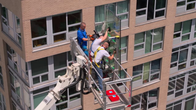 the construction team preparing for the high-altitude job using the lifting platform. harlem, new york city - hoisting stock videos & royalty-free footage