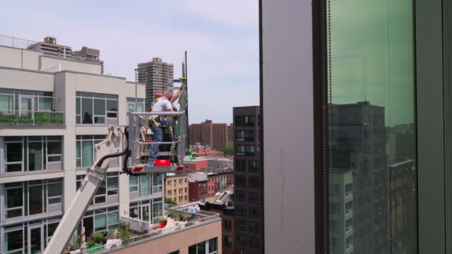 the construction team preparing for the high-altitude job using the lifting platform. harlem, new york city - installing stock videos & royalty-free footage