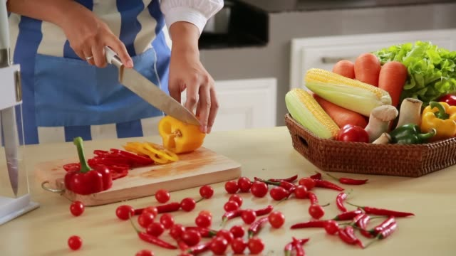 The Cook in Blue apron cuts vegetables. The concept of eco-friendly products for cooking