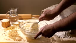 The cook mixes the dough in a glass bowl