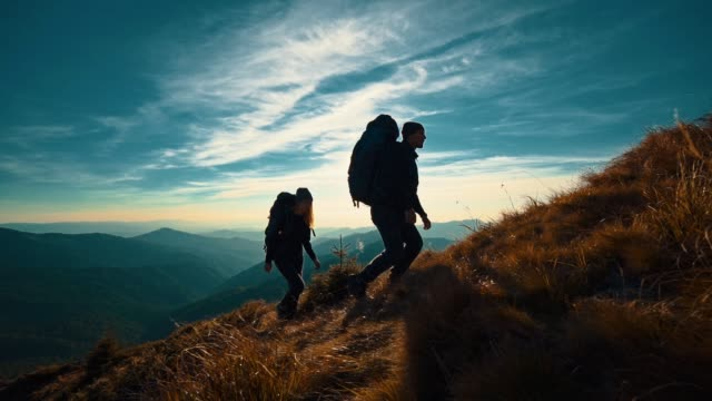 The couple with camping backpacks walking to the mountain top. slow motion