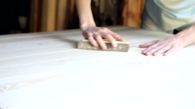 die handwerker verarbeitet die holzoberfläche der künftigen tabelle. - standing stock-videos und b-roll-filmmaterial