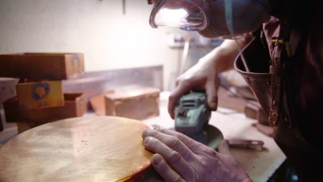 vídeos y material grabado en eventos de stock de el artesano que lleva gafas protectoras y el delantal de cuero puliendo los detalles de latón con la herramienta eléctrica - bronceado