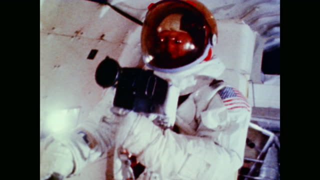 The crew of Apollo 11 Neil Armstrong Buzz Aldrin and Michael Collins practice gathering moonrocks wearing spacesuits and working in zero gravity in...