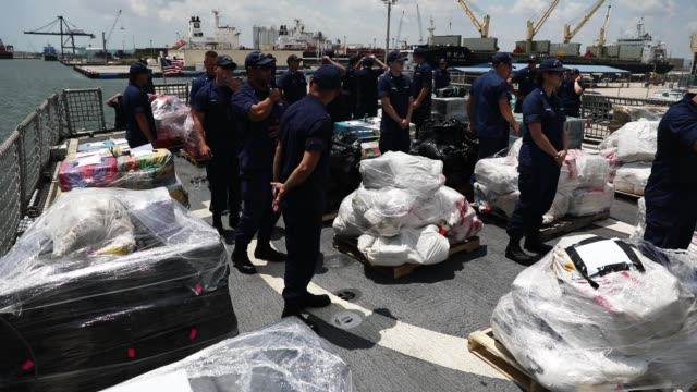 the crew of the coast guard ship legare stands among wrapped packages of approximately 12 tons of cocaine and 1 ton of marijuana before offloading... - narcotic stock videos & royalty-free footage