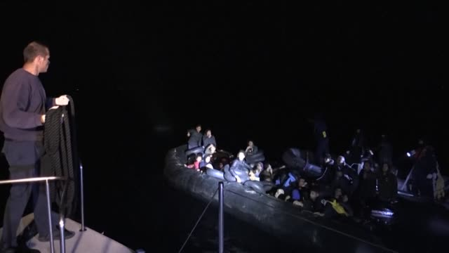 vídeos de stock e filmes b-roll de the crew of the greek coastguard patrol boat jumps to life as they pull 48 migrants out of a rubber dinghy in the sea off the island of samos - samos