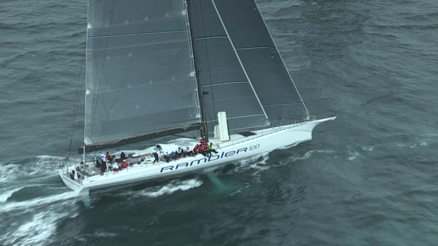 The crew of the high-tech racing yacht, Rambler 100, comes up to the windward side to sit on the rail for the best weight displacement during a race.