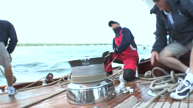 the crew of the velsheda yacht adjusts the line on a nautical winch during a yacht race near newport, rhode island. - segelsport stock-videos und b-roll-filmmaterial