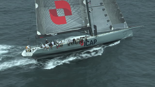 The crew on the giant racing yacht, ICAP Leopard, are seated on the windward rail of the boat.