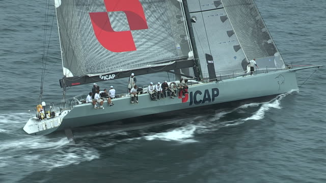 The crew on the giant racing yacht, ICAP Leopard, checks the sails and trim on their boat during a TransAtlantic Race.