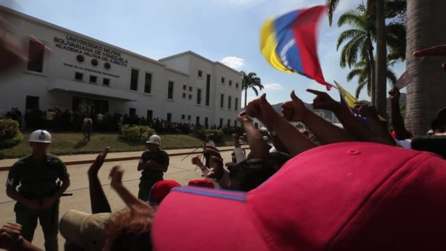 the crowd cheers at the conclusion of the funeral for venezuelan president hugo chavez at the military academy on march 8 2013 in caracas venezuela... - ウゴ・チャベス点の映像素材/bロール