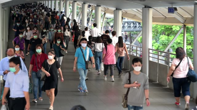 the crowd is wearing protective masks prevent coronavirus, covid 19 virus during virus outbreak and pm2.5 air pollution crisis rush hour bangkok, thailand - hart arbeiten stock-videos und b-roll-filmmaterial