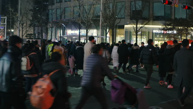 the crowd of people walking in busy shopping street area in south korea city life at night - street name sign stock videos & royalty-free footage