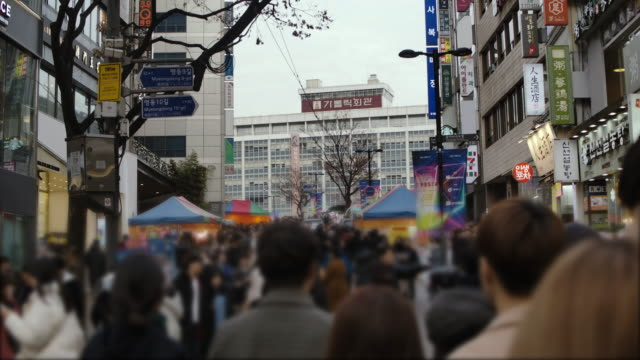 the crowd of people walking in busy shopping street area in south korea city life - street name sign stock videos & royalty-free footage