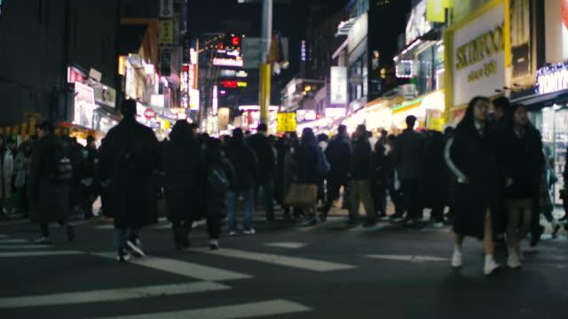 die menschenmenge, die nachts in einer belebten einkaufsstraße in südkorea saust - gehweg stock-videos und b-roll-filmmaterial