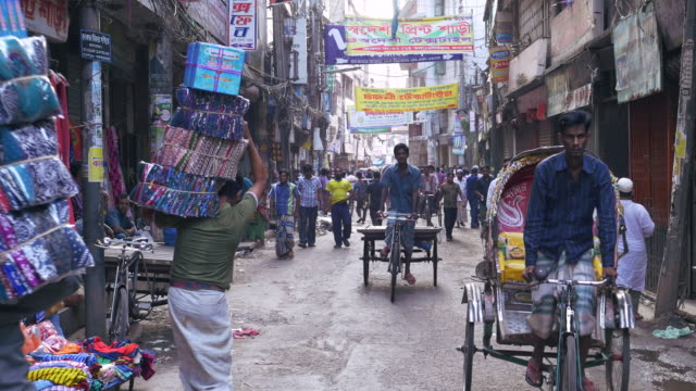 The crowded alleyways and streets of the old part of Dhaka Bangladesh are bustling with pedestrians and rickshaws