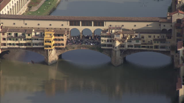 the crowded ponte vecchio crosses the arno river in florence, italy. - tuscany stock videos & royalty-free footage