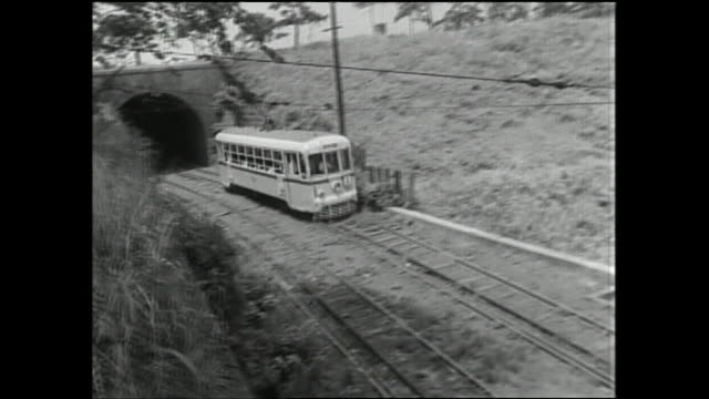 the crowded toei streetcar leaves a tunnel and speeds downhill on its dedicated track. - passenger点の映像素材/bロール