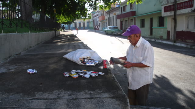 vídeos de stock e filmes b-roll de the cuban government pays for the return of the aluminum contained in the cans some people make income by collecting the cans from public places and... - triturar atividade
