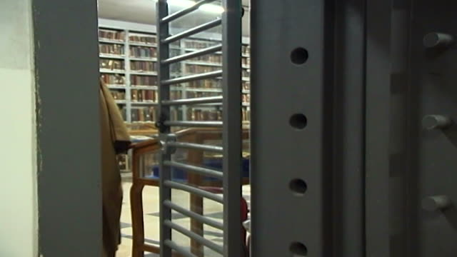 the curator of the marachi najafi library opens the vault doors to a room filled with antique books, manuscripts and qurans. the curator and an... - curator stock videos & royalty-free footage