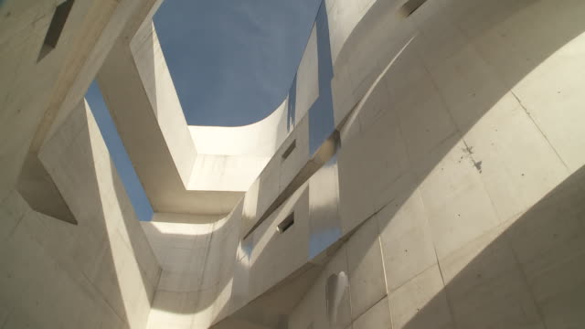 the curved walls of ibere camargo foundation museum frame patches of blue sky in porto alegre, brazil. - sculpture stock videos & royalty-free footage