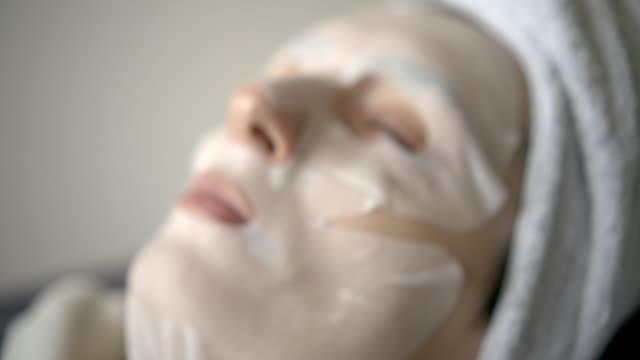 vídeos de stock, filmes e b-roll de a menina bonito com uma máscara limpa que relaxa - dermatologia