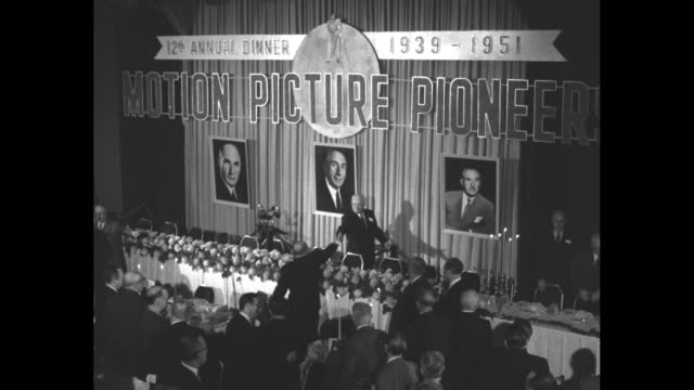 the dais at the waldorf astoria fills with the 3 warner brothers and 20 men / the brothersõ portraits hang behind the dais /audience gives a standing... - warner bros stock videos & royalty-free footage