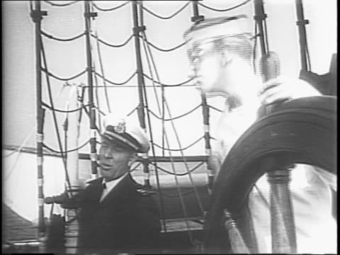 the danish flag is raised onto the danmark's mast seen from two angles / wide view of the danmark at the pier / sailors at the helm of the ship... - helm stock videos & royalty-free footage