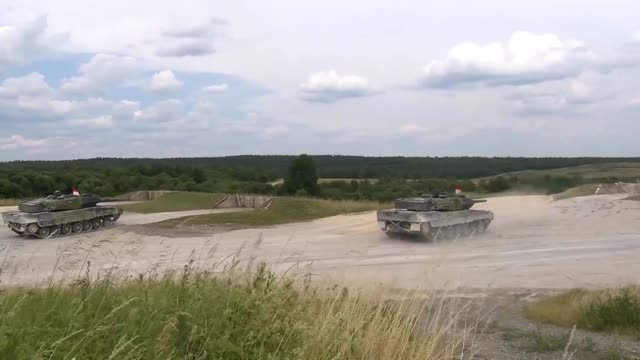 The Danish Royal Army conducts a live fire training exercise with Leopard 2 fighting tanks at the 7th Army Joint Multinational Training Command's...