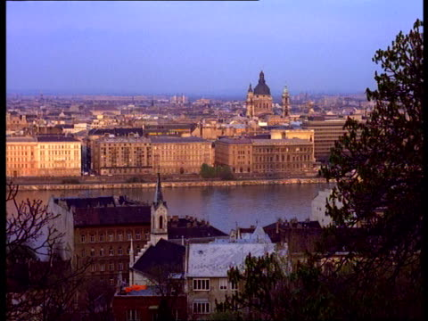 The Danube River flows past buildings near St. Stephens Church in Budapest, Hungary.