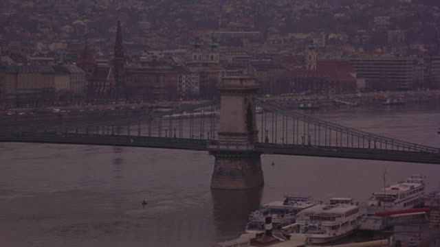 vídeos de stock e filmes b-roll de the danube river flows under budapest's chain bridge. - ponte das correntes ponte suspensa