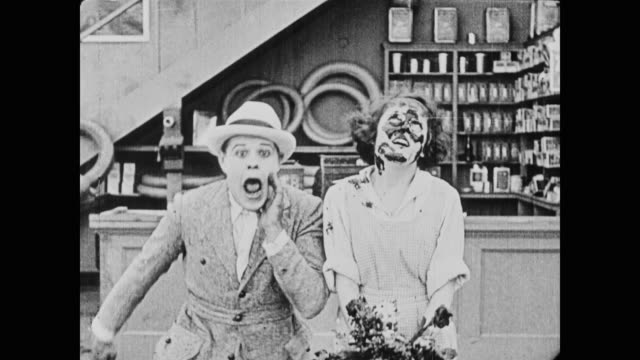 1920 the daring and athletic molly gets upset with her suitor when he hands her flowers that he had mistakenly dipped in men's (buster keaton and fatty arbuckle) oil pan - fatty arbuckle stock videos and b-roll footage