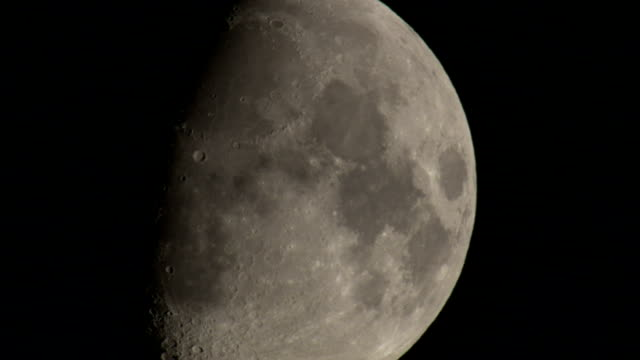 the dark sky contrasts with the bright side of the moon. available in hd. - luna video stock e b–roll