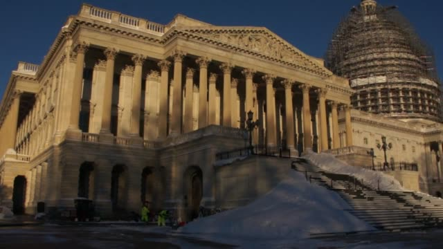 The day after a massive blizzard hit Washington a Capitol police officer descends the West Front steps a truck plows by the Senate steps under the...