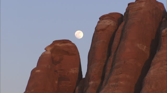 the daylight moon peeks through rock formations in canyonlands national park in utah. - canyonlands national park stock videos & royalty-free footage