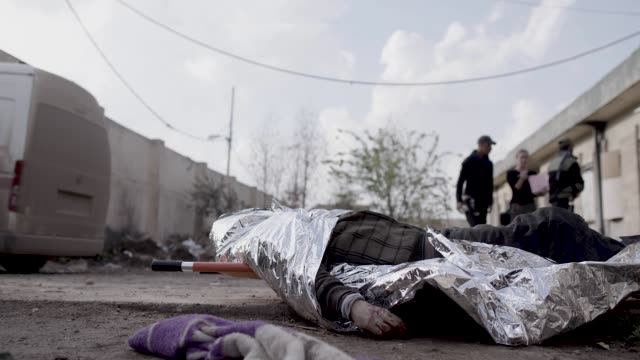 the dead body of a civilian lies on the ground outside of a iraqi army field hospital in mosul. the military operation to liberate the city of mosul... - civilian stock videos & royalty-free footage