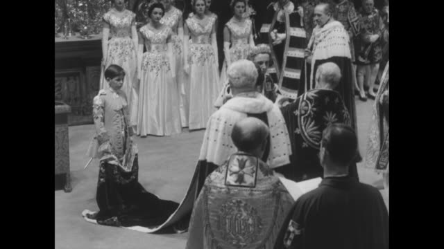 the dean of westminster and mistress of robes place the robe royal around elizabethõs shoulders/ ws maids of honor / choir is heard singing god save... - coronation stock videos and b-roll footage