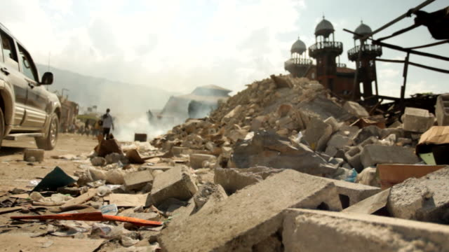 the debris of buildings that had storefront in the street and people walking in the ruined city after the haiti earthquake of january 2010 - port au prince stock videos & royalty-free footage