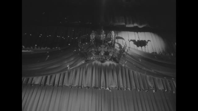 WS of the decoration crown and draping above the stage at the Imperial Ball spotlights on them / WS stage with Chrysler Imperial in background and...