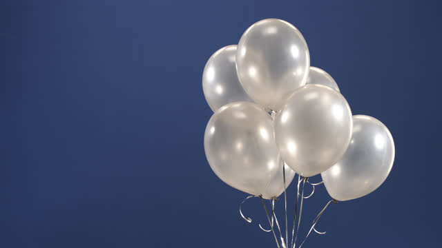 the decorative element - balloons - fly into the frame on the video as a surprise for the holidays: valentine's day, birthday, christmas or new year on a blue background. - silver coloured stock videos & royalty-free footage