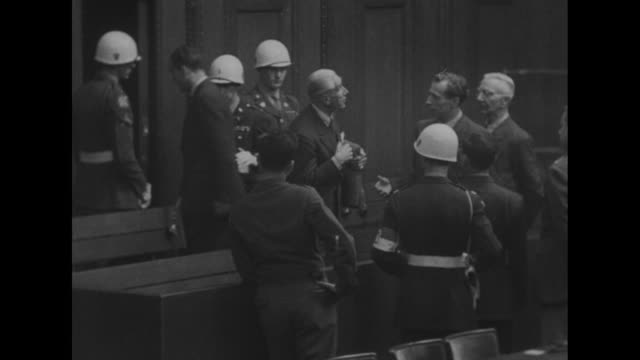 vs the defendants talk among themselves in the courtroom dock and some exit the room with whitehelmeted american military guards / high angle view of... - processi di norimberga video stock e b–roll