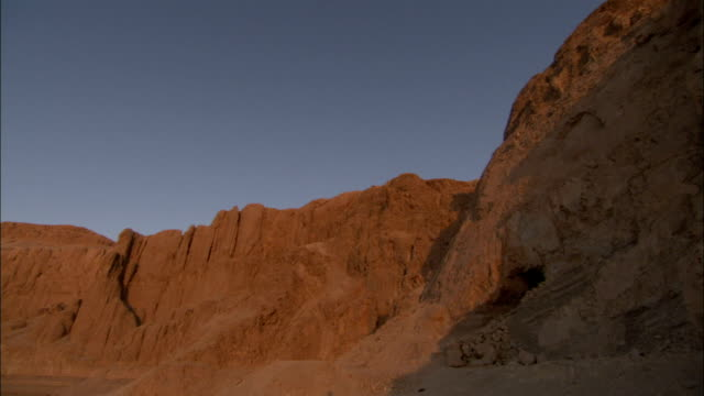 the deir el bahari cliffs tower over the temple of hatshepsut in egypt. available in hd. - hatschepsut tempel stock-videos und b-roll-filmmaterial