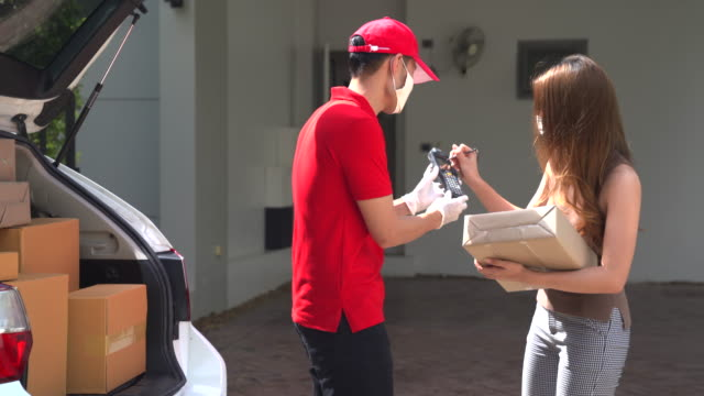 the delivery staff handed the parcel to the customer with a barcode gun. let customers sign their name. applicable to the work of the transportation of packages. online purchases during the quarantine period during the virus outbreak. - customer focused stock videos & royalty-free footage