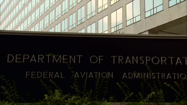 the department of transportation federal aviation administration has a sign in front of its office building in washington, dc. - federal building stock videos and b-roll footage
